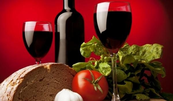 Бутилка и две чаши червено вино, хляб и зеленчуци